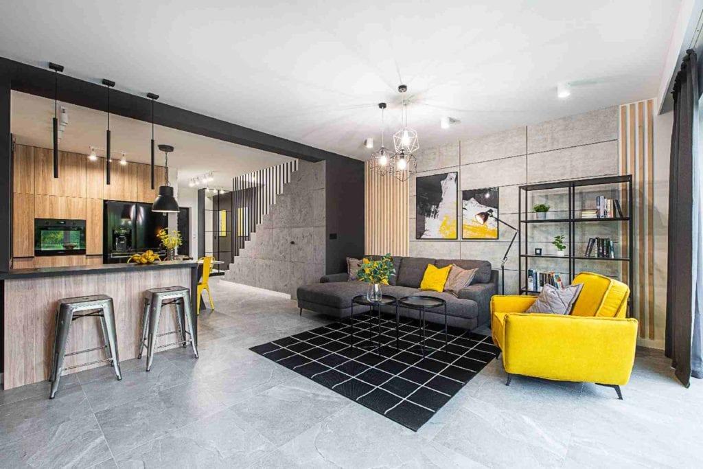 Pracownia Dobry Układ Sandra Białkowska i apartament w stylu soft loft - salon z szarą kanapą i żółtym fotelem