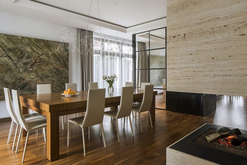 Pracownia Inter-Arch Architekci i luksusowa rezydencja w Wilanowie - drewniany stół z kompletem krzeseł w salonie