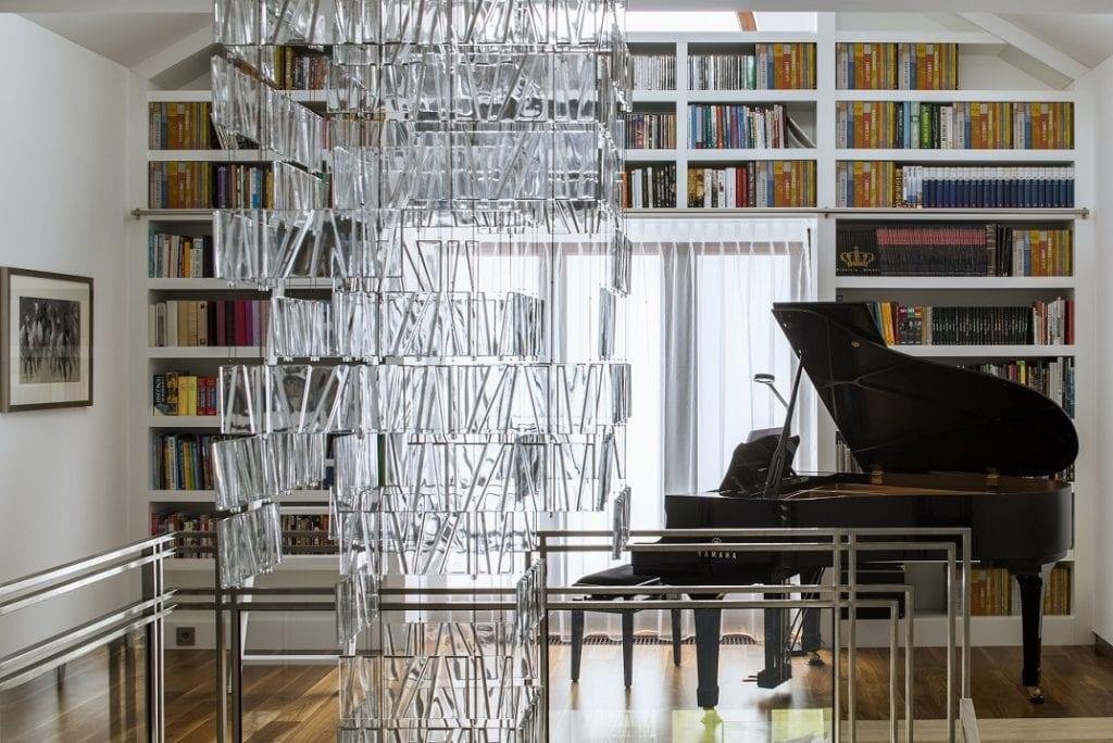 Pracownia Inter-Arch Architekci i luksusowa rezydencja w Wilanowie - fortepian w pokoju z książkami