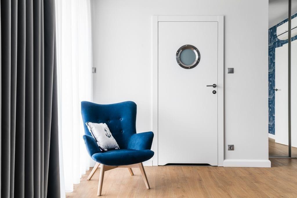 Wakacyjny dom w Giżycku projektu Studio Projekt x Dekorian Home - zdjęcia Fotomohito - niebieski fotel w pokoju