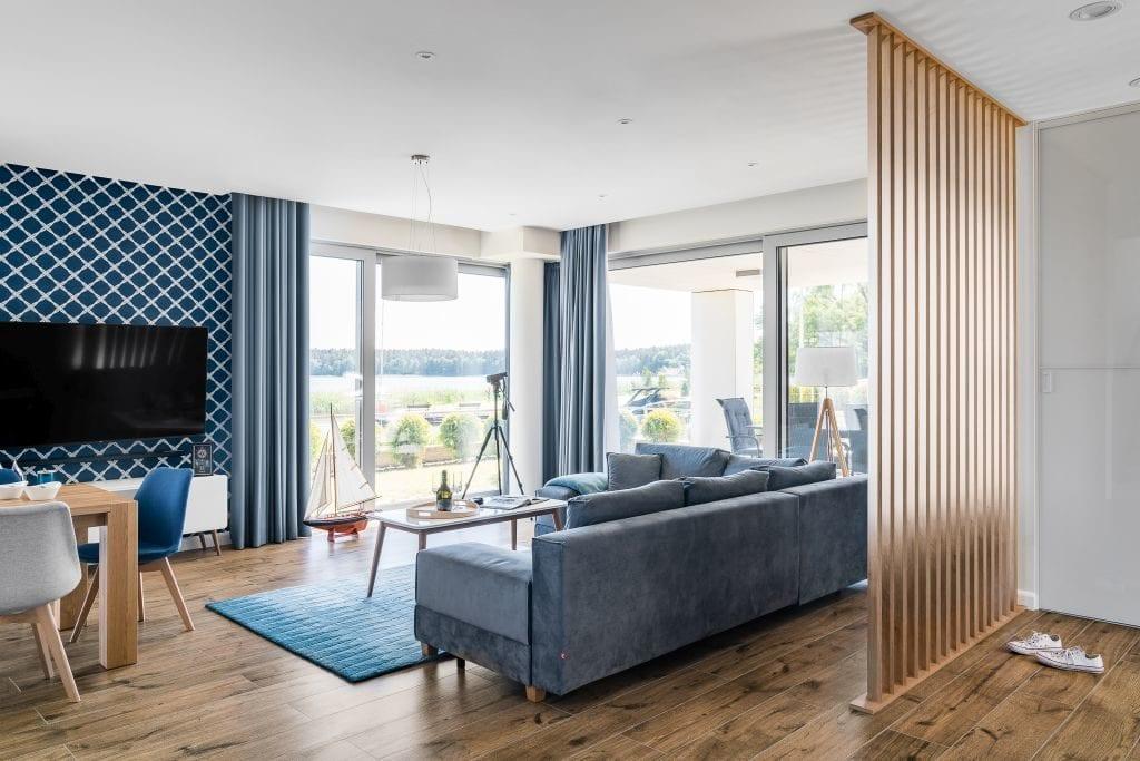 Wakacyjny dom w Giżycku projektu Studio Projekt x Dekorian Home - zdjęcia Fotomohito - salon z niebieską kanapą