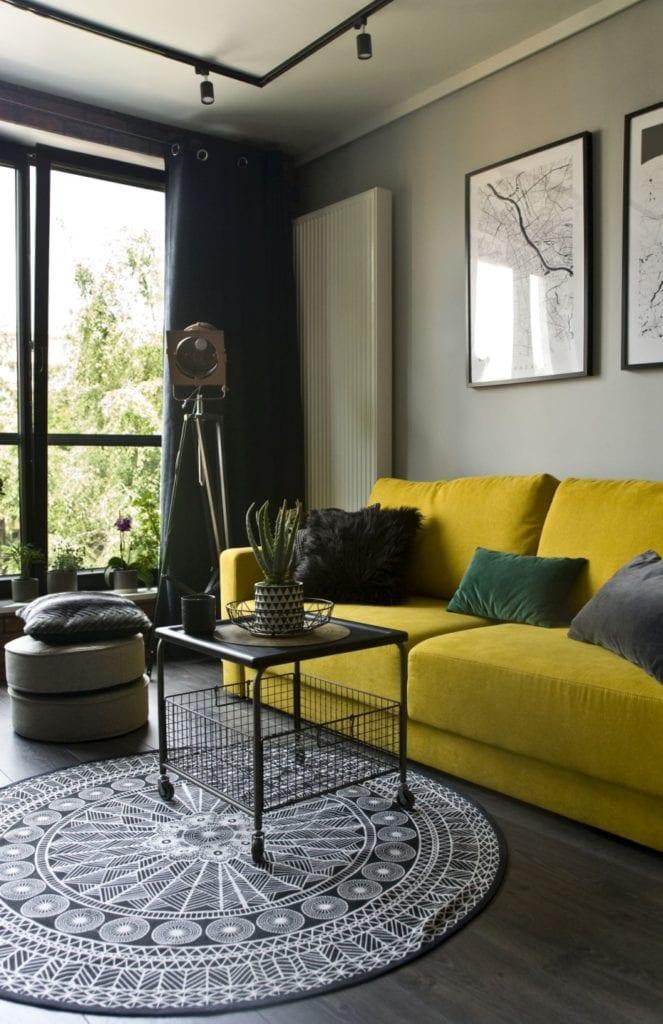 Za co kochamy styl loftowy? Projekt Miśkiewicz Design - Magdalena Miśkiewicz - stolik stojący przy żółtej sofie w salonie