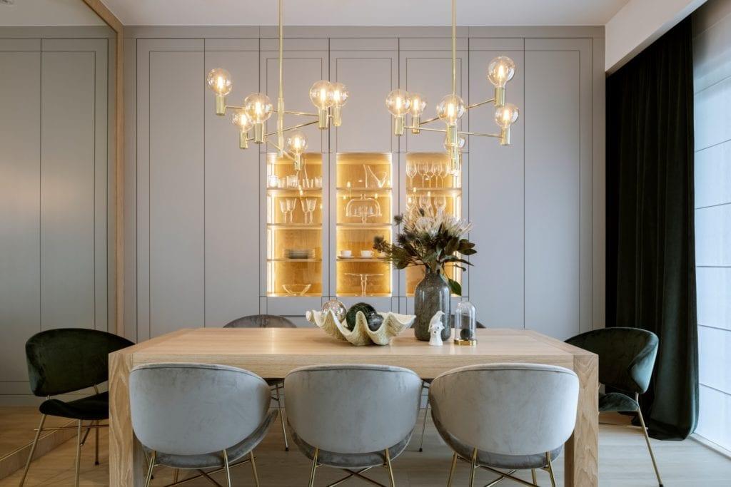 Dom projektu HOLA Design w świątecznej stylizacji - salon z drewnianym stołem i zestawem krzeseł