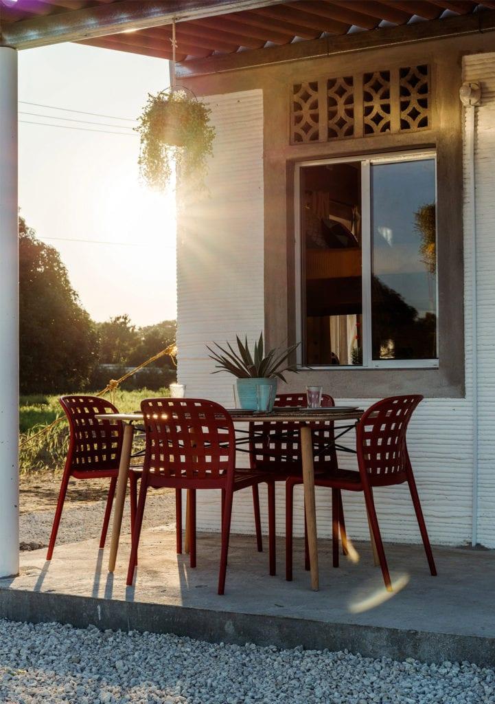 Domy z drukarki 3D w miejscowości Tabasco w południowym Meksyku - projekt New Story ICON i fuseproject - krzesła przed domem