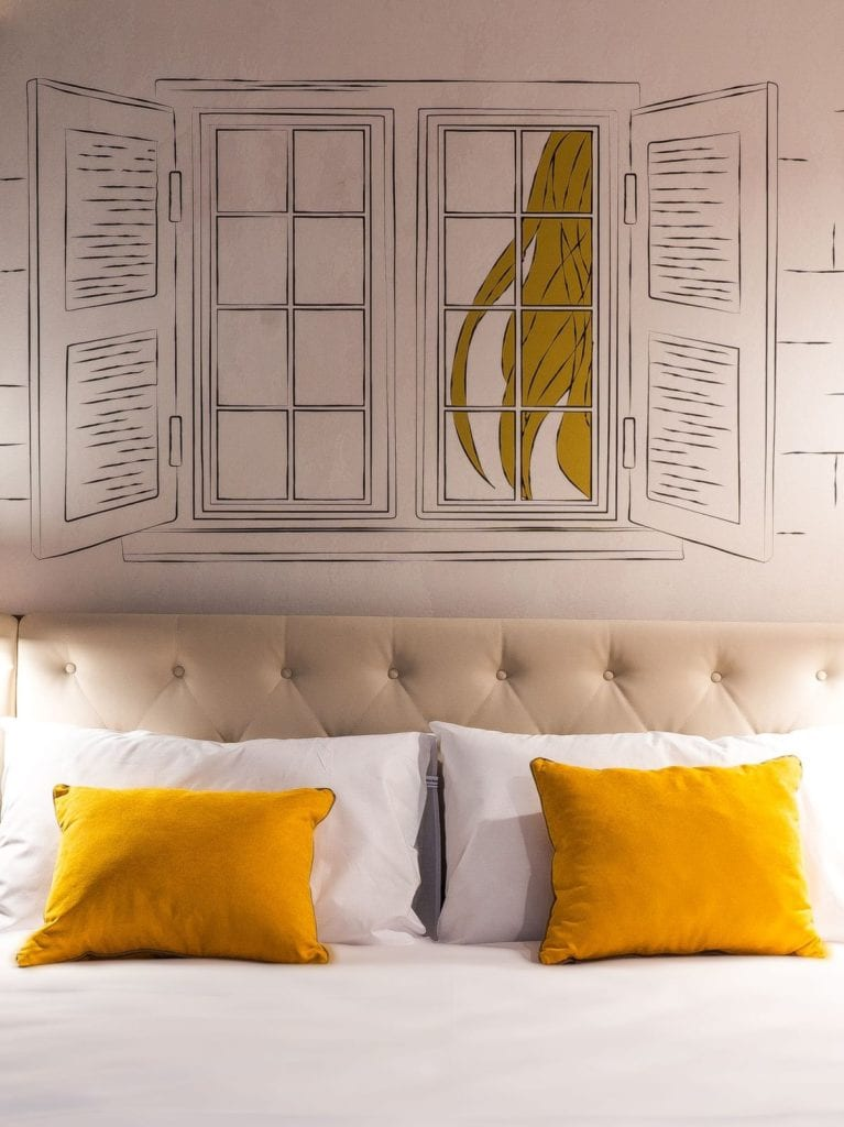 Ibis Styles Lublin Stare Miasto projektu pracowni Tremend - pokój z żółtymi poduszkami na łóżku