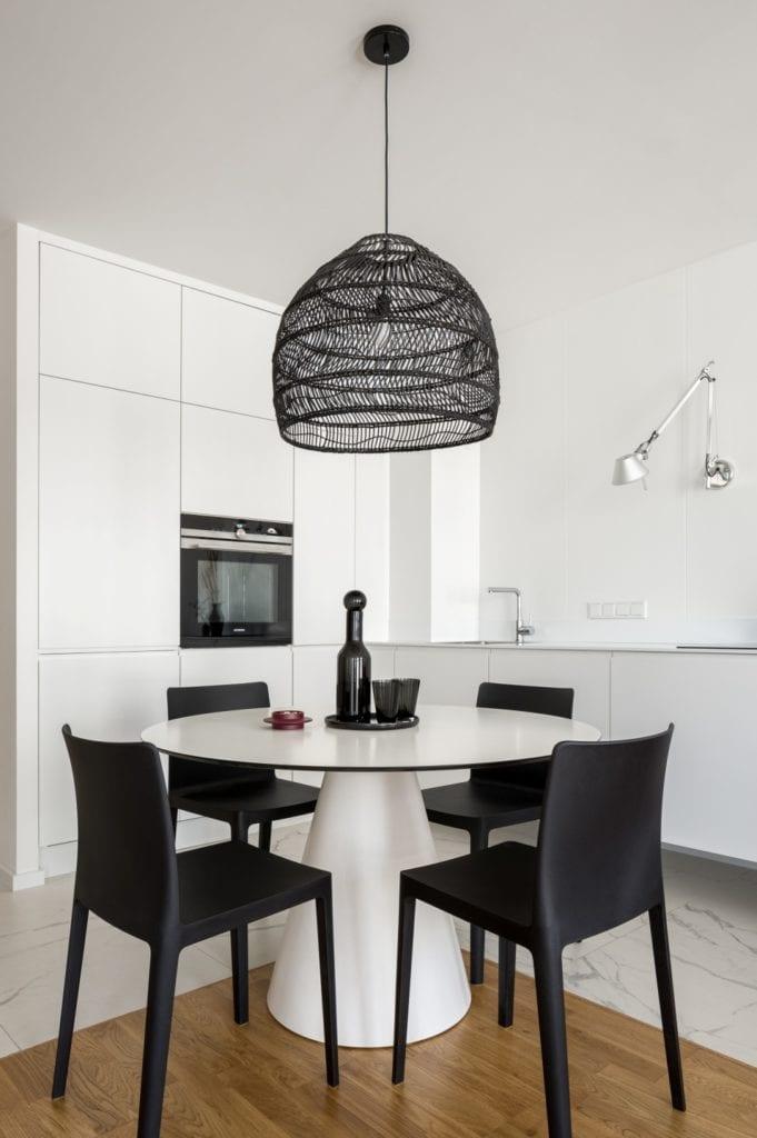 Kawalerka w Łodzi projektu pracowni 3XEL Architekci - okrągły biały stół i cztery czarne krzesła
