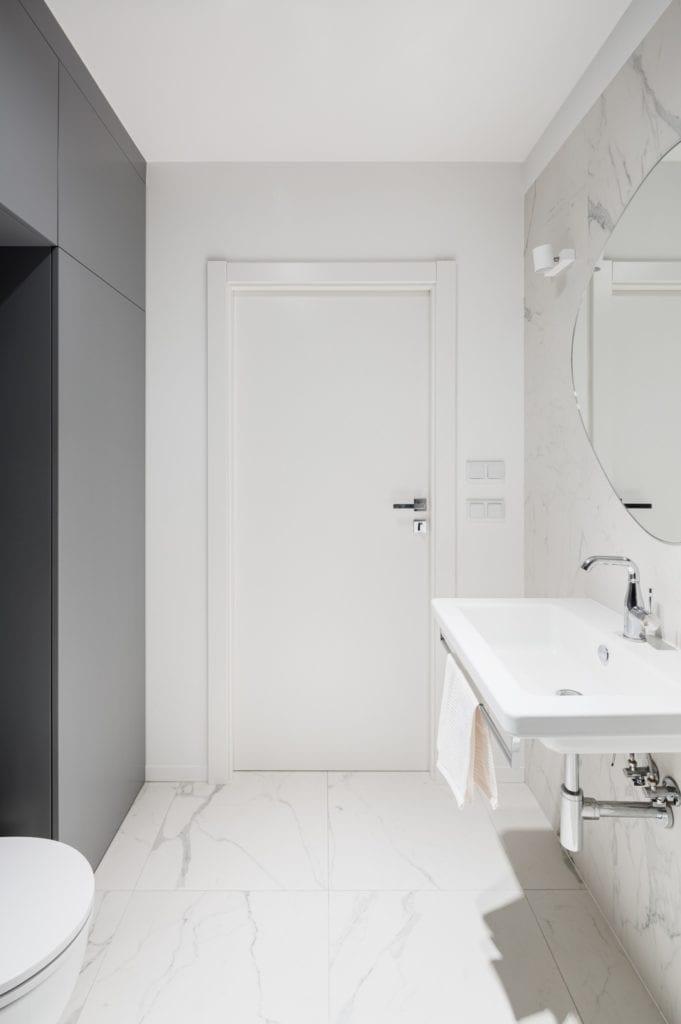 Kawalerka w Łodzi projektu pracowni 3XEL Architekci - białe drzwi w łazience