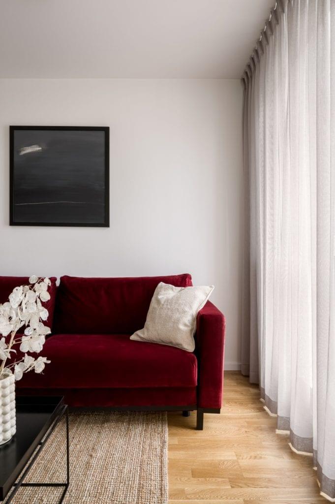 Kawalerka w Łodzi projektu pracowni 3XEL Architekci - bordowa sofa w salonie