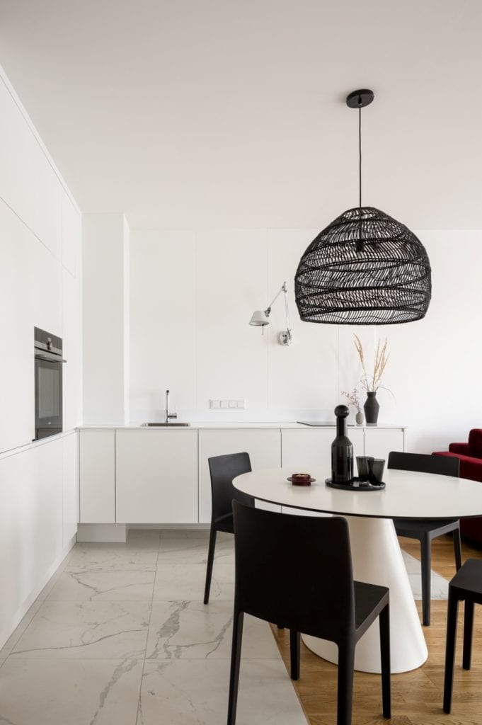 Kawalerka w Łodzi projektu pracowni 3XEL Architekci - białe meble w salonie