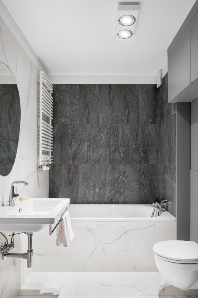 Kawalerka w Łodzi projektu pracowni 3XEL Architekci - szare płytki w łazience