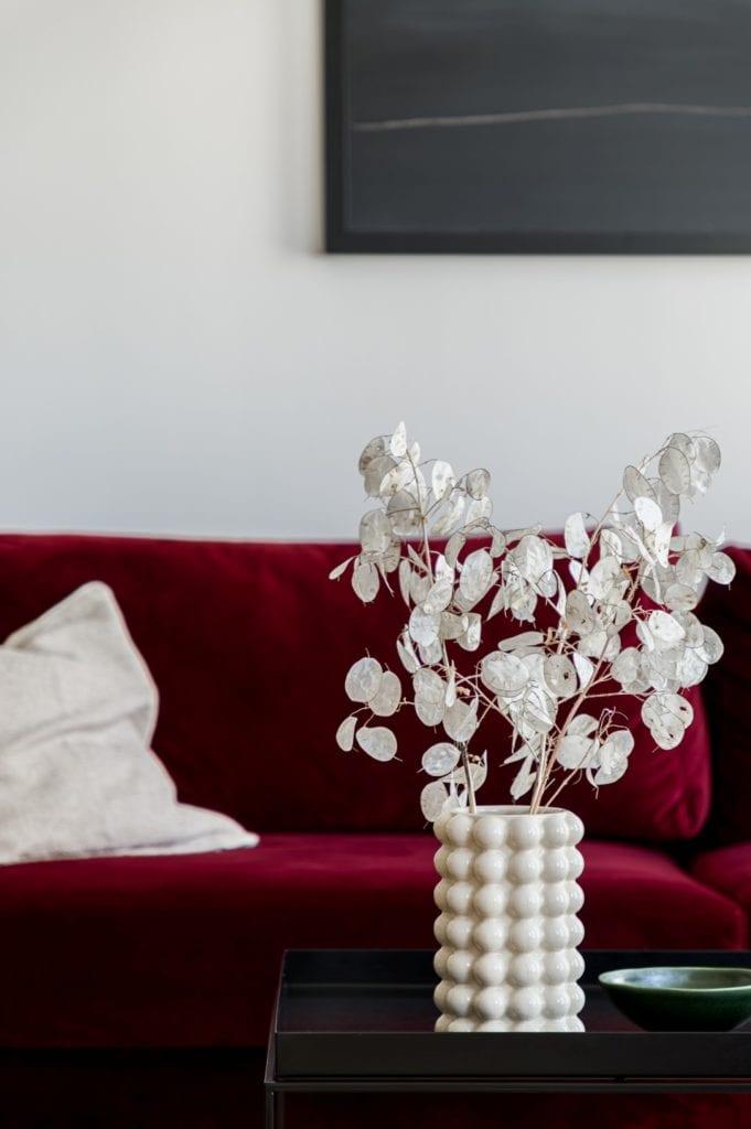 Kawalerka w Łodzi projektu pracowni 3XEL Architekci - bordowa kanapa i biały wazon