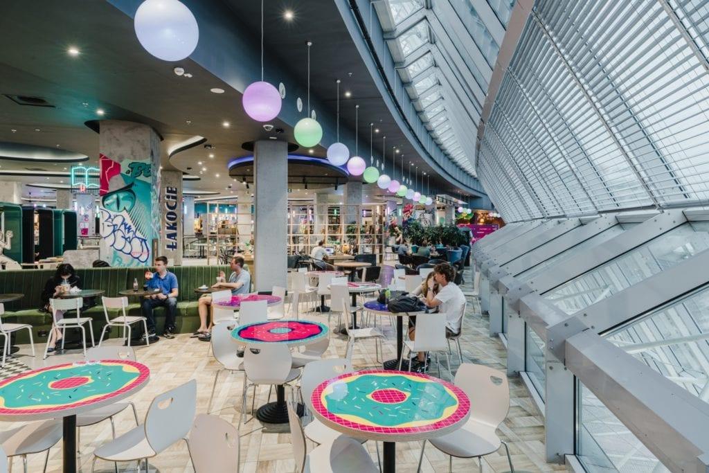 Kolorowe stoliki w Foodstacji w Pasażu Grunwaldzkim projektu pracowni MIXD