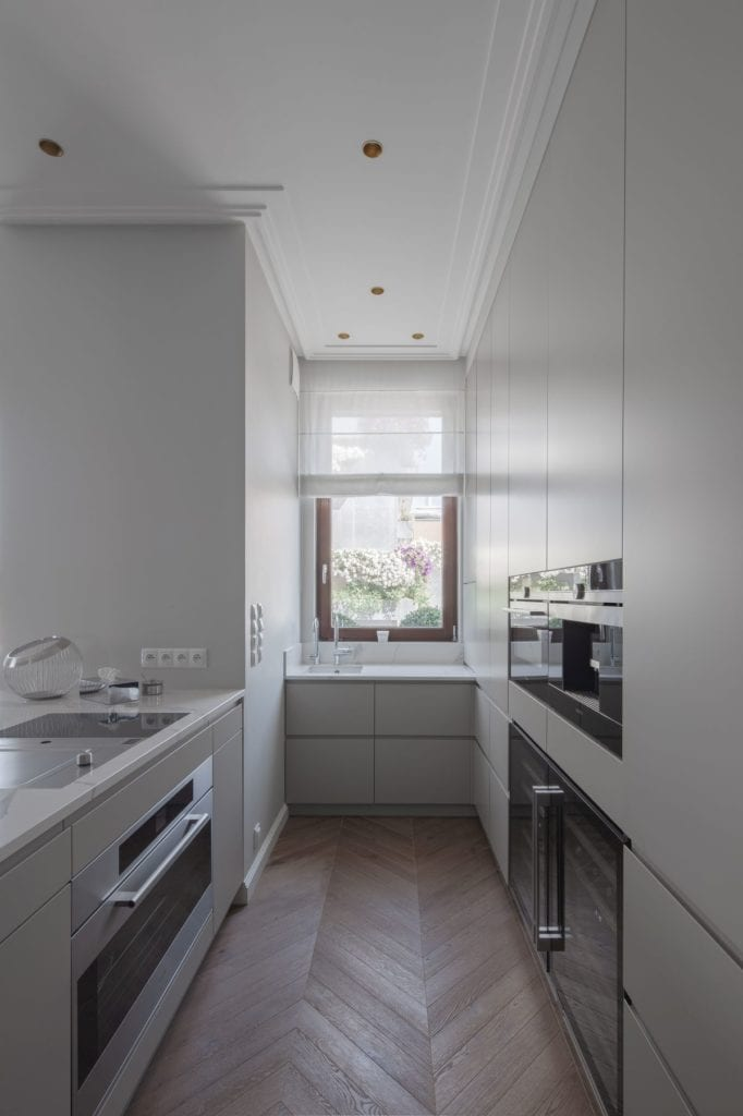 Nowoczesny i komfortowy apartament projektu Pauliny Taff - kuchnia z białą zabudową