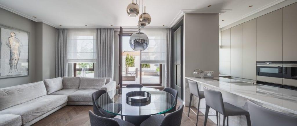 Nowoczesny i komfortowy apartament projektu Pauliny Taff - okrągły stół z krzesłami w salonie