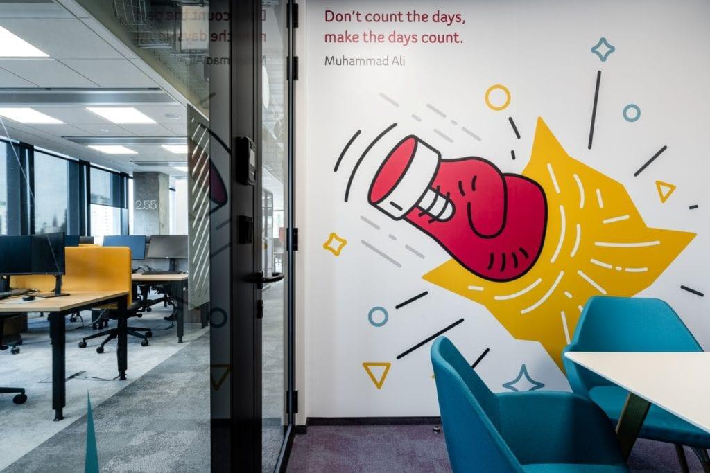 Warszawskie biuro UPC projektu The Design Group - grafika na ścianie z rękawicą bokserską