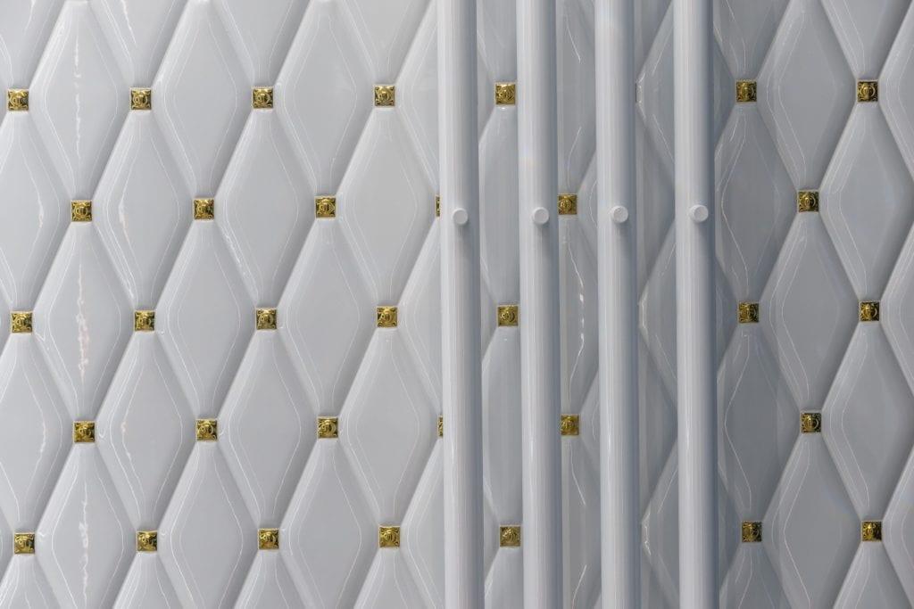 Białe płytki łazienkowe ze złotymi detalami