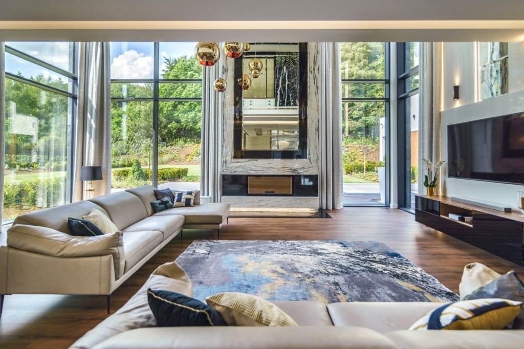 Przestronny, wysoki salon z ogromną sofą i pięknym widokiem