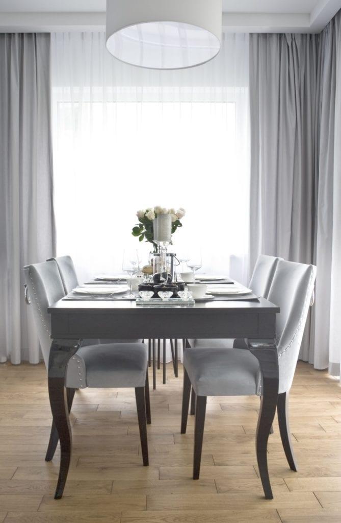 Drewniany stół z kompletem krzeseł w sypialni