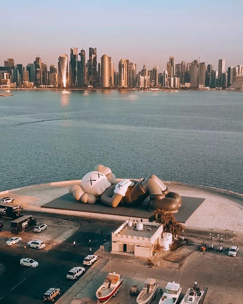 KAWS - Brian Donnelly i instalacja artystyczna na tle panoramy miasta Doha