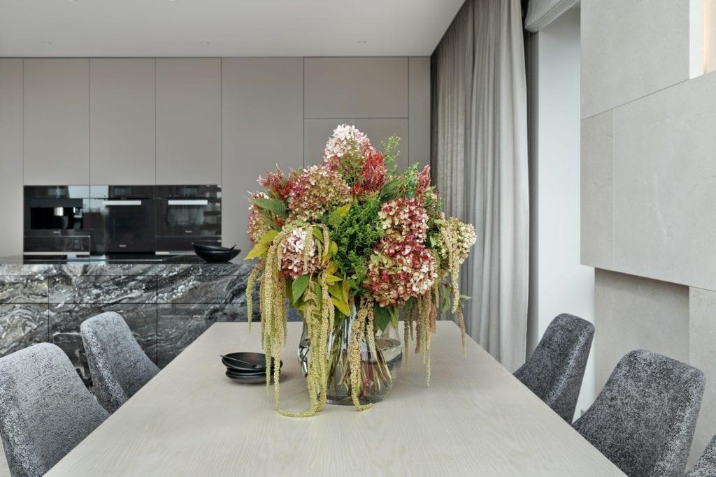 Wazon z kwiatami stojący na drewnianym stole