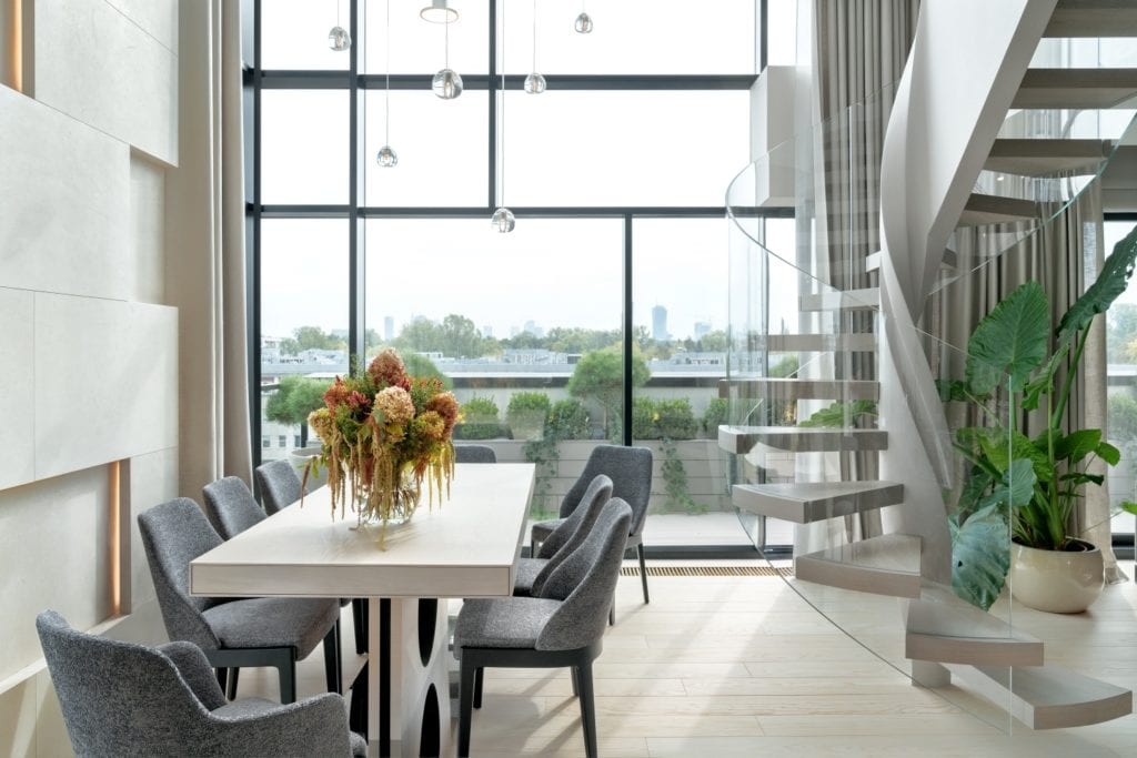 Drewniany stół z kompletem krzeseł w salonie w warszawskim apartamencie