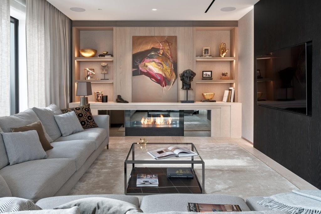 Ogromny salon z szarą sofą, stolikiem i obrazem nad kominkiem