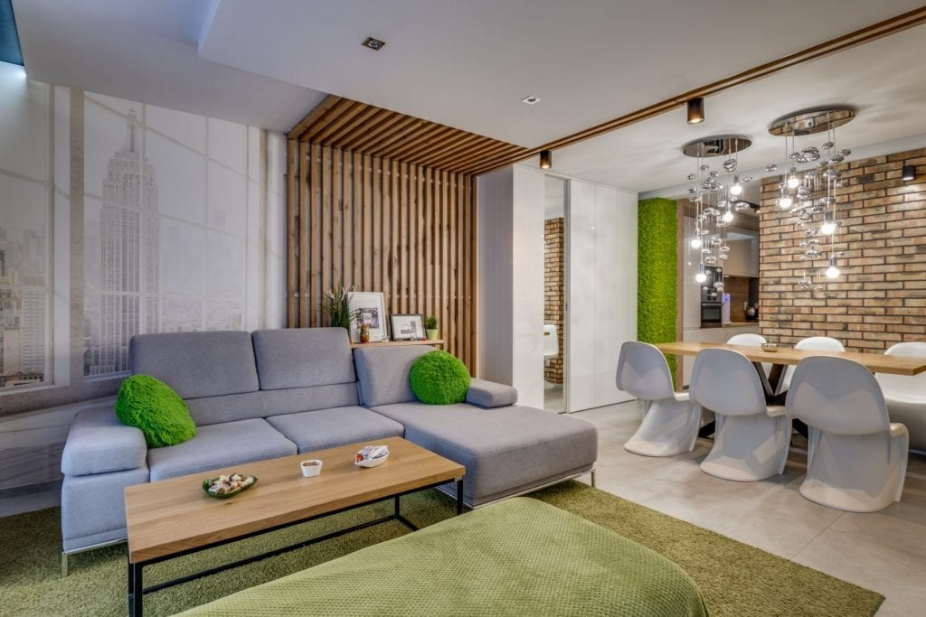 Szara narożna sofa w salonie w mieszkaniu projektu Marmo Design