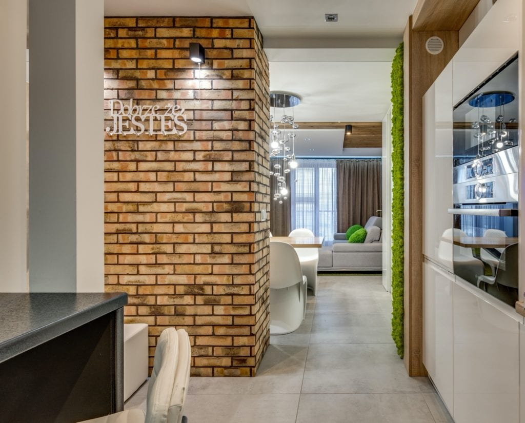 Cegła na ścianie w salonie w mieszkaniu projektu Marmo Design