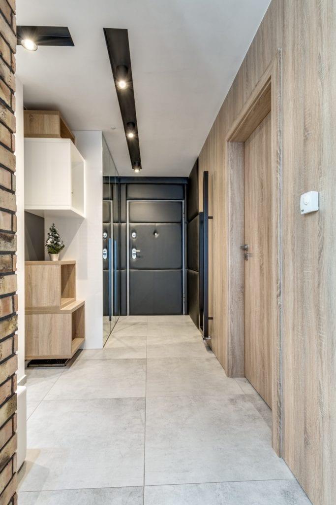 Przedpokój z drewnianymi elementami w mieszkaniu projektu Marmo Design