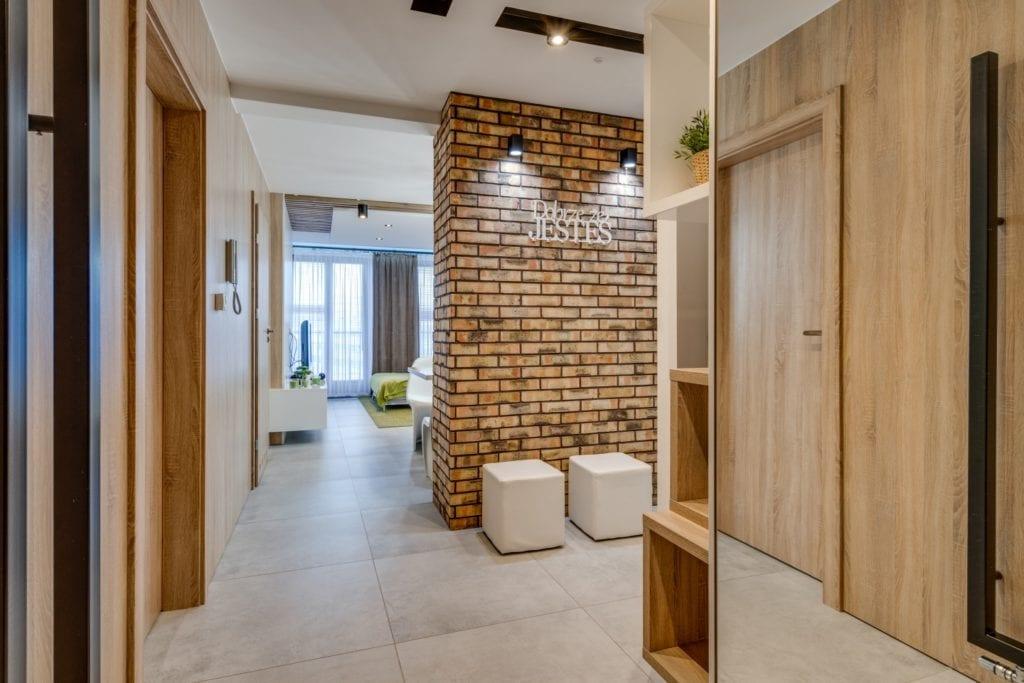 Przedpokój z cegłą na ścianie w mieszkaniu projektu Marmo Design