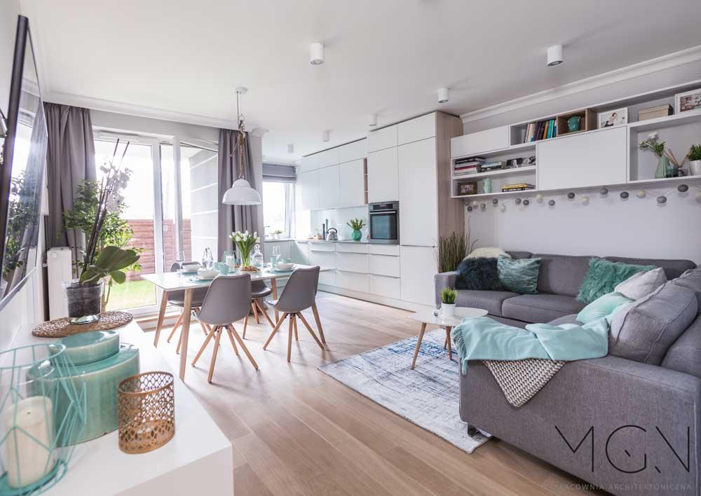 Salon połączony z kuchnią, a w nim duży narożnik i stół z kompletem krzeseł