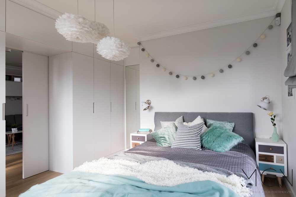 MGN Pracownia Architektoniczna i jasna sypialnia z dużym łóżkiem z miętowymi dodatkami