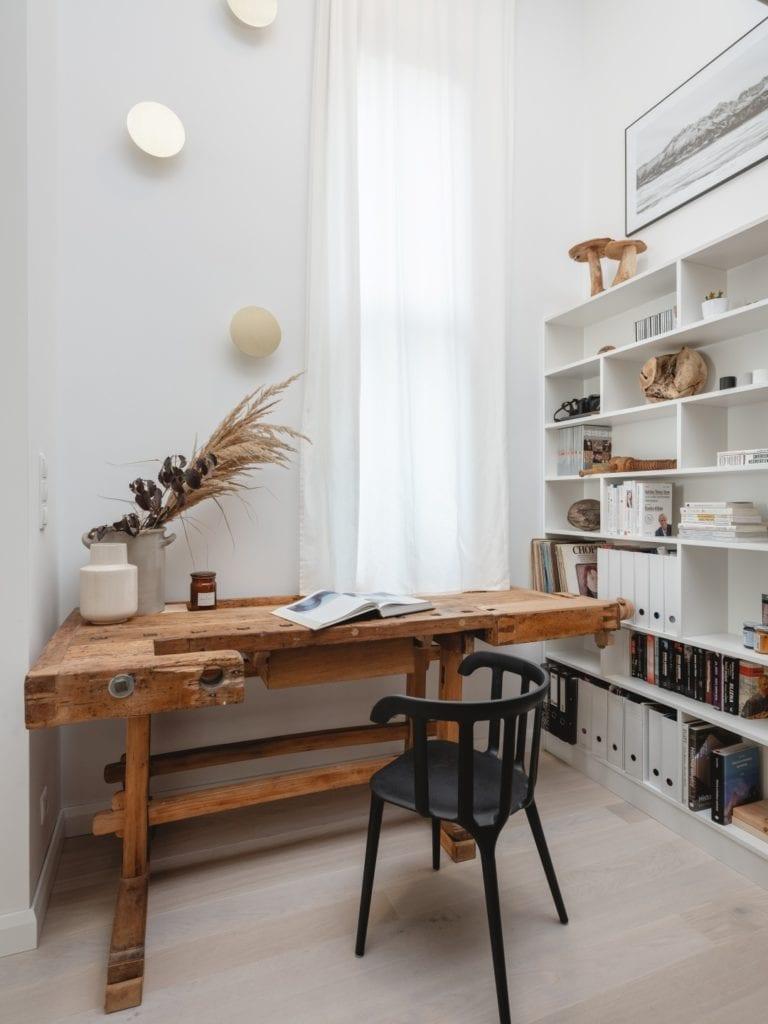 Mieszkanie architektki Karoliny Gacy z pracowni GRUPA NONO - drewniany stół stojący obok regału