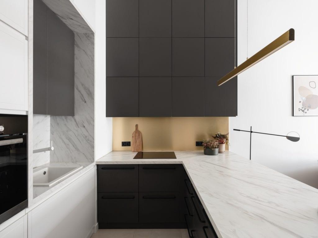 Mieszkanie architektki Karoliny Gacy z pracowni GRUPA NONO - część kuchenna z ciemnymi meblami
