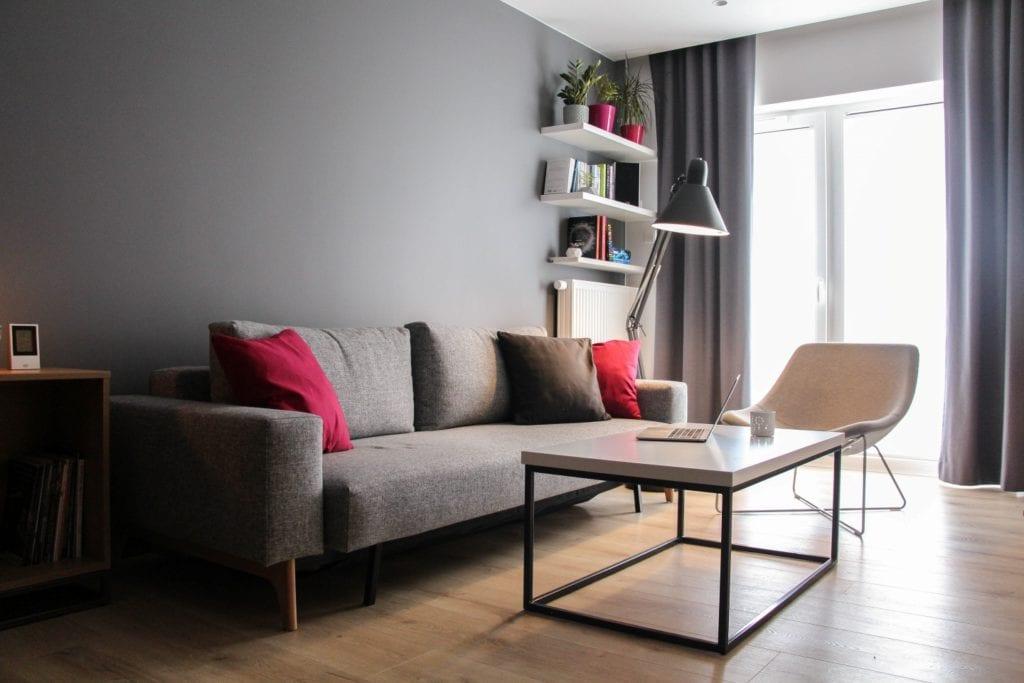 Szara sofa w pokoju z szarą ścianą w poznańskim mieszkaniu projektu 3XB Architekci