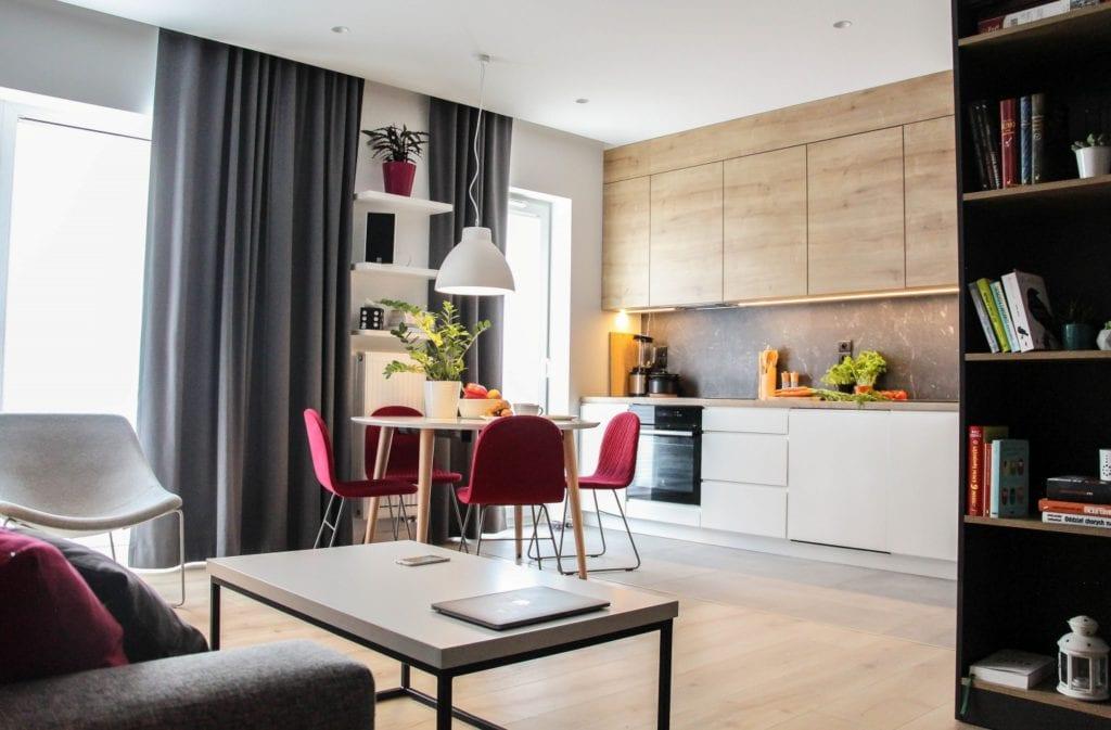 Salon połączony z kuchnią w poznańskim mieszkaniu projektu 3XB Architekci