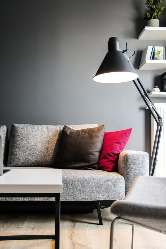 Szara ściana i szara sofa w poznańskim mieszkaniu projektu 3XB Architekci