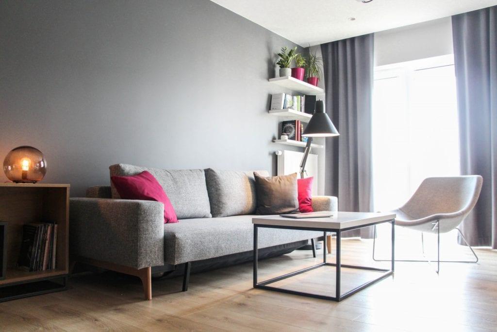 Szara sofa i kwadratowy stolik w poznańskim mieszkaniu projektu 3XB Architekci