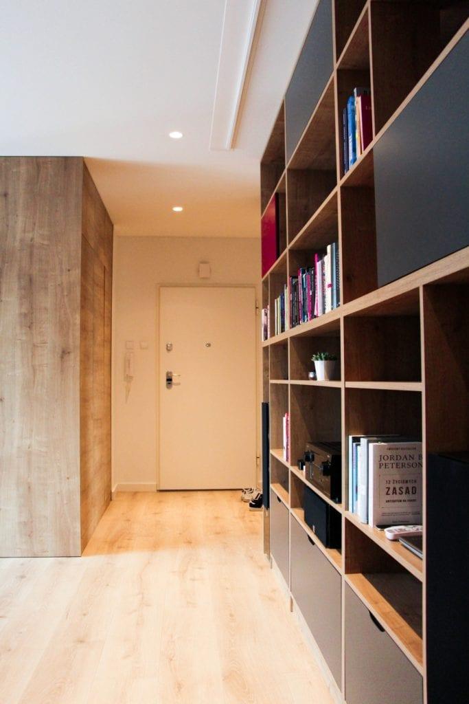 Regał na książki w holu w poznańskim mieszkaniu projektu 3XB Architekci