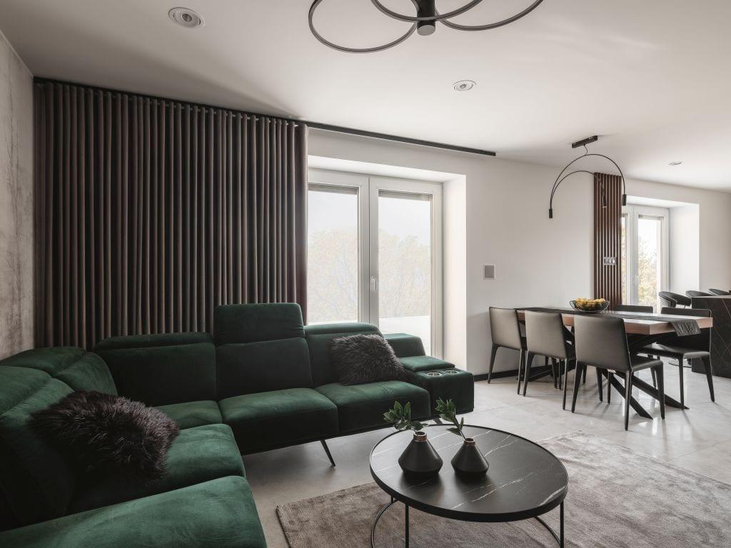 Kaza Interior Design i mieszkanie w Suchedniowie - zielony narożnik stojący w przestronnym salonie