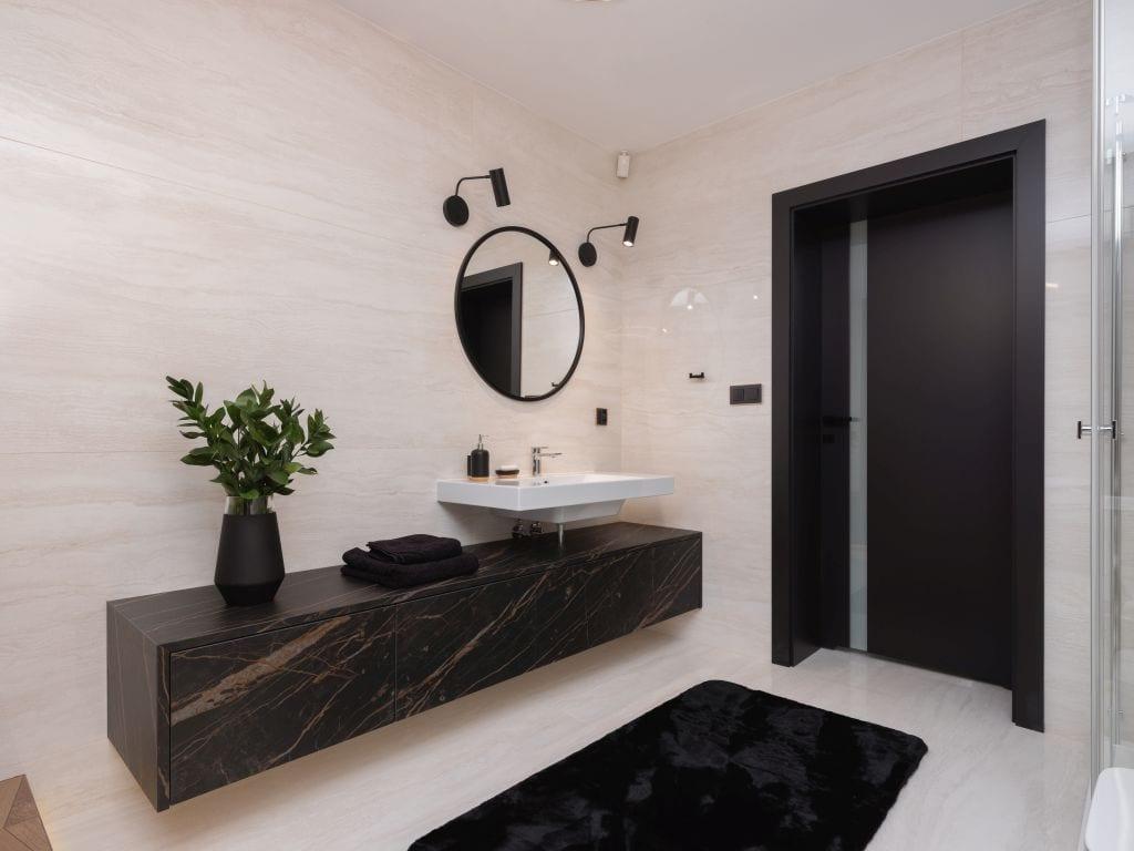 Kaza Interior Design i mieszkanie w Suchedniowie - jasna łazienka z czarnym blatem i czarnymi drzwiami łazienkowymi
