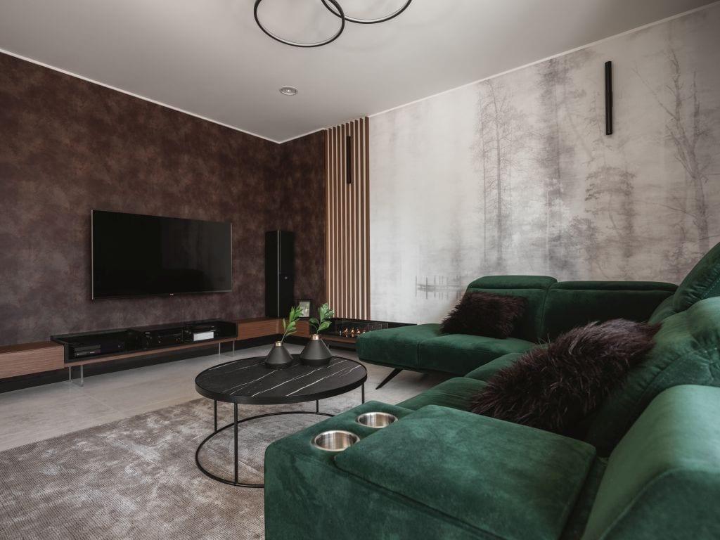Kaza Interior Design i mieszkanie w Suchedniowie - narożnik w kolorze butelkowej zieleni i stojący przy nim okrągły stolik