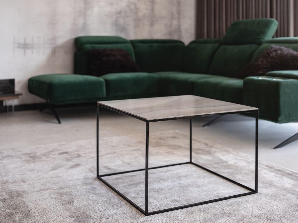 Kaza Interior Design i mieszkanie w Suchedniowie - kwadratowy stolik stojący przy narożniku w kolorze butelkowej zieleni