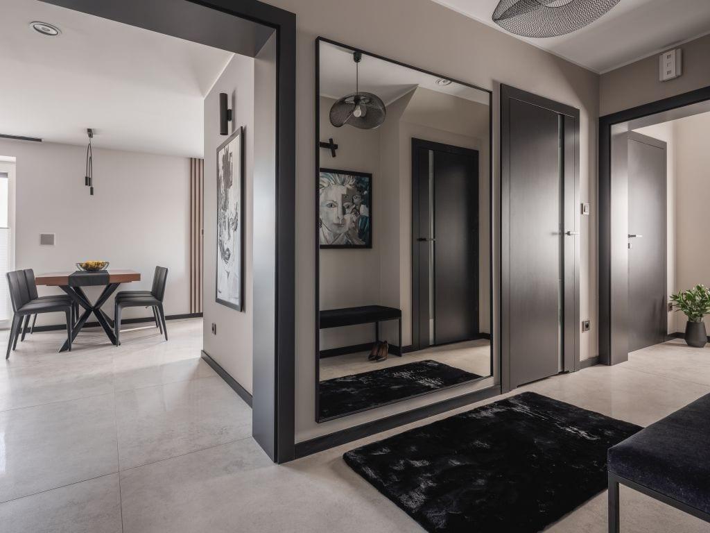 Duże, pionowe lustro wiszące w holu mieszkania zaprojektowanego przez Kaza Interior Design