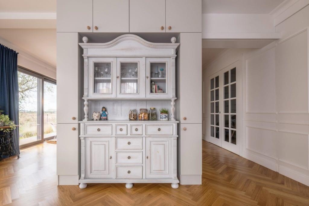 Komoda w stylu prowansalskim w przestronnym salonie z drewnianym parkietem