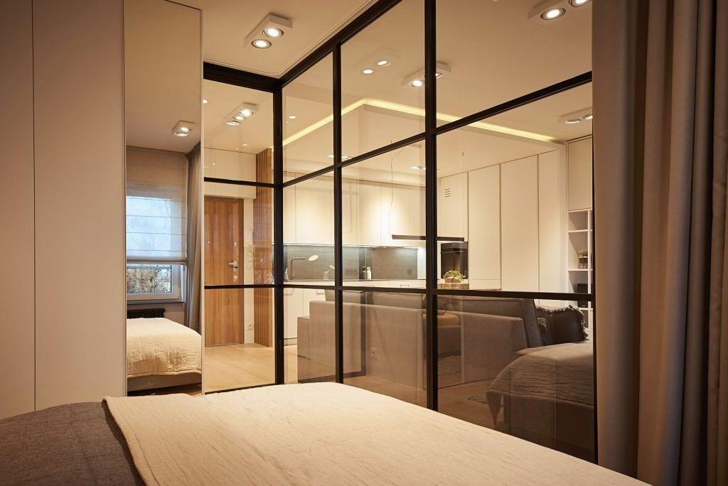 Szklana ściana oddzielająca dwa pomieszczenia w mieszkaniu projektu Martyny Midel