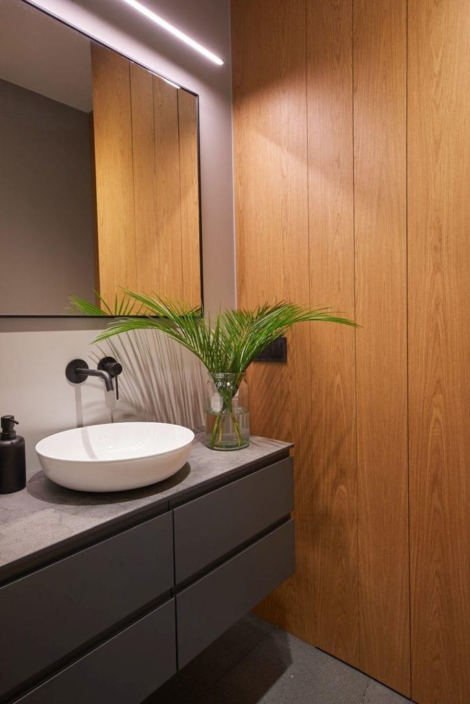 Okrągła umywalka stojąca na blacie w łazience