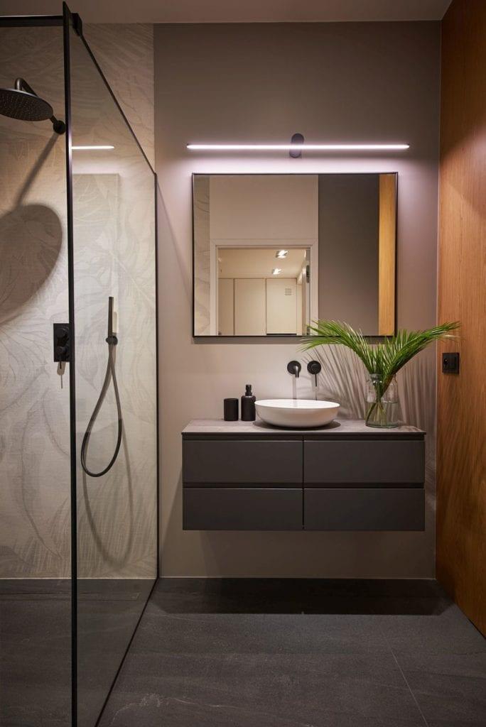 Łazienka z kwadratowym lustrem na ścianie