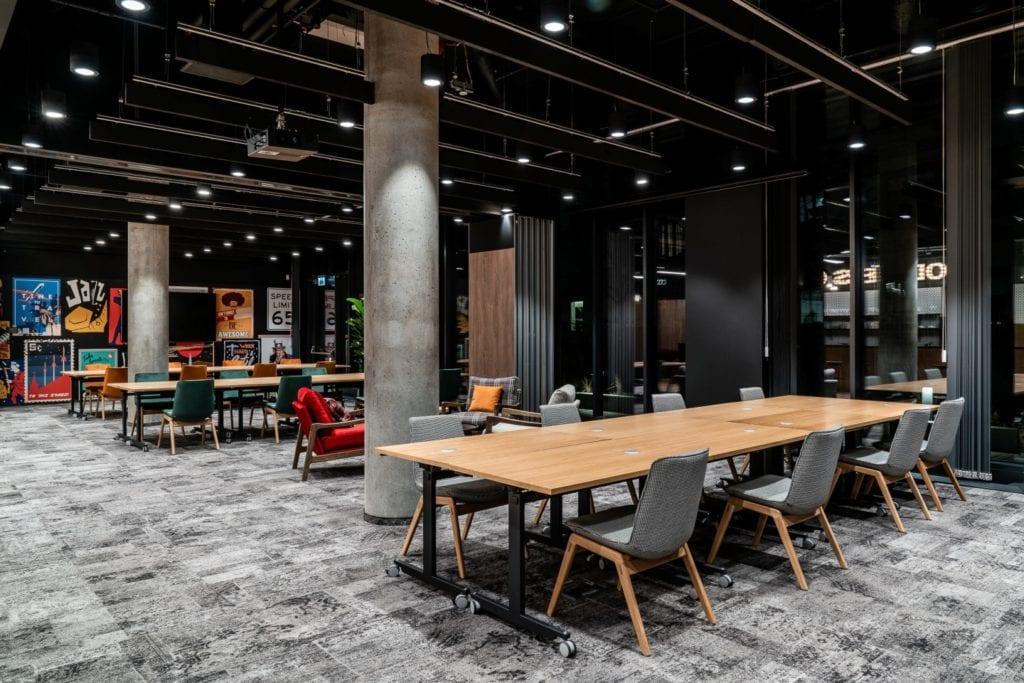 Drewniany stół będący jednocześnie miejscem do pracy w coworku Solutions Rent