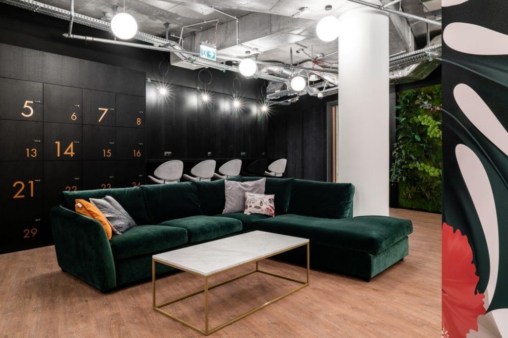 Sofa w kolorze butelkowej zieleni w coworku Solutions Rent